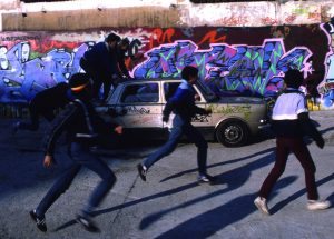 Henry Chalfant, Boys chase abandoned car past Stalingrad graffiti wall, Paris, 1985, Macro, Cross the Streets